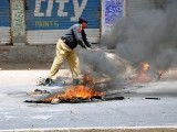 Policeman removes burning tires from a road in Faisalabad. PHOTO: ONLINE