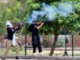 Policemen fire teargas to disperse protesters in Faisalabad. PHOTO: ONLINE