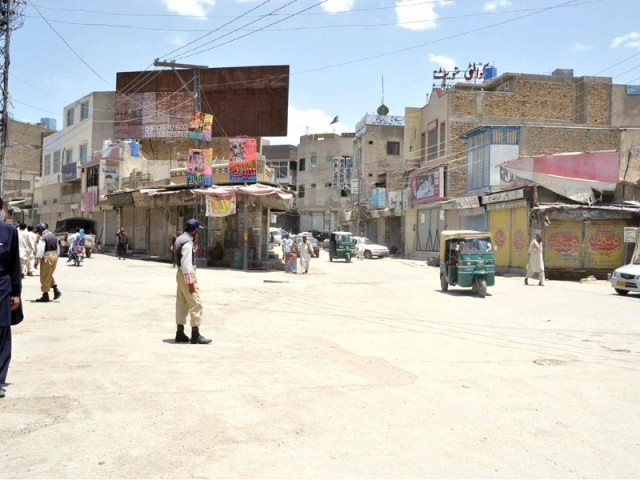 Policemen stand guard during a shutter-down strike in Quetta on Friday. PHOTO: PPI