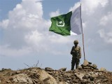a-pakistani-soldier-poses-for-a-photo-under-pakistans-national-flag-planted-atop-the-baine-baba-ziarat-mountain-in-swat-district-2-2-2-2-2-3-2-2