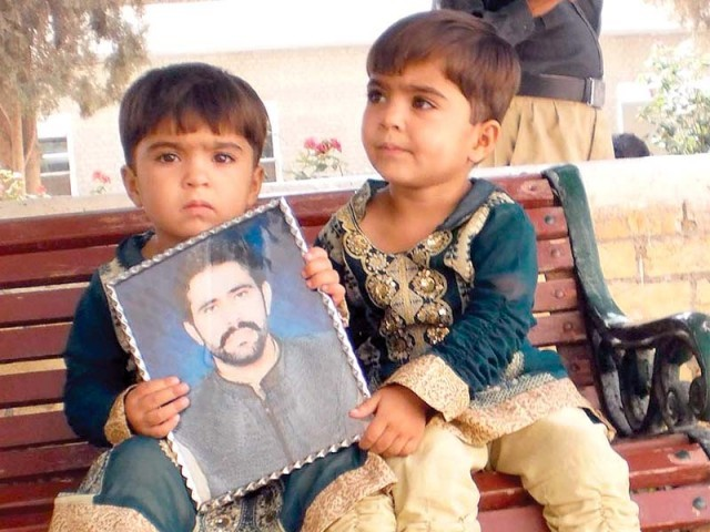 Two children hold a picture of their missing father in Quetta outside the hearing on the missing persons case. PHOTO: INP/ FILE