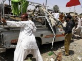 Activists of the Awami National Party (ANP) help move a damaged truck following a bomb blast in Quetta on July 13, 2012. PHOTO: AFP