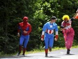 Fans disguised as, LtoR, comics characters, Super Man, Captain America and as a clown, wait on the roadside for riders during the 226 km and twelfth stage of the 2012 Tour de France cycling race starting in Saint-Jean-de-Maurienne and finishing in Annonay Davezieux, southeastern France, on July 13, 2012. PHOTO: AFP