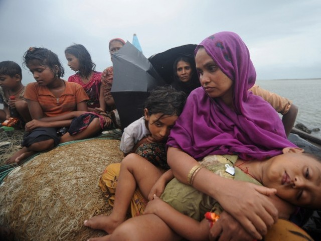 This file picture taken on June 13, 2012 shows Rohingya Muslims, trying to cross the Naf river into Bangladesh to escape sectarian violence in Myanmar, look on from an intercepted boat in Teknaf. PHOTO: AFP