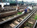 Indian passengers sit on the railway tracks near the platform of Sealdah train station waiting for the resumption of services during a power failure in Kolkata on July 31, 2012. PHOTO: AFP