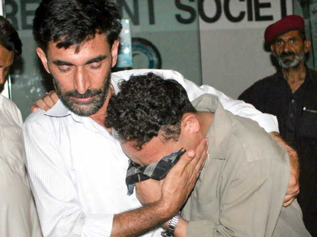 A man comforts a mourner, following the attack on a passenger van in Mansehra. PHOTO: AFP