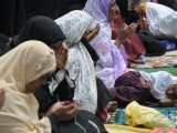 A child rests as Indian Muslim women offer Jumat-ul-Vida prayers on the last Friday of Ramazan outside the historic Mecca Masjid in Hyderabad on August 17, 2012, ahead of the Eid ul-Fitr festival. PHOTO: AFP
