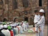 A boy holds a child next to Muslims offering last Friday prayers at the ruins of the Feroz Shah Kotla mosque ahead of the Eid ul-Fitr in New Delhi August 17, 2012. PHOTO: REUTERS