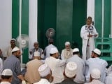A Muslim cleric (top R) delivers a sermon to devotees during Jumat-ul-Vida, the last Friday of the holy month of Ramazan, in the compound of Hazratbal shrine in Srinagar August 17, 2012. PHOTO: REUTERS