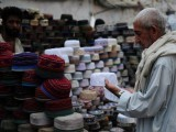 A Pakistani shopper selects a cap for the upcoming holy fasting month of Ramazan at a roadside shop in Karachi on July 19, 2012.  PHOTO: AFP