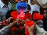 A Pakistani Muslim distributes juice to children after they broke their fast at a park in Lahore on July 21, 2102, on the first day of the month of Ramazan. PHOTO: AFP