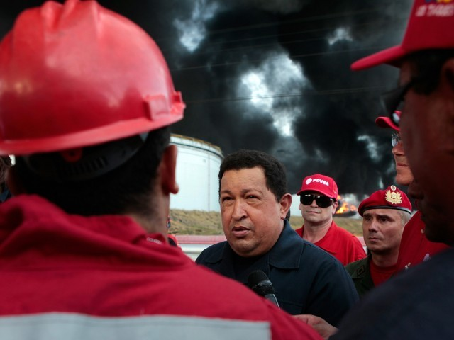Venezuelan President Hugo Chavez (C) talks to oil workers while visiting the Amuay oil refinery a day after an explosion in Punto Fijo on August 26, 2012.  The devastating fire that followed an explosion at Venezuela's main oil refinery was still burning strong, as Chavez surveyed the carnage that killed 41 people. PHOTO: AFP/FILE