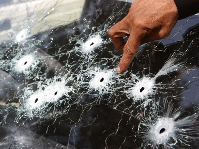 Policeman inspect a car attacked by gunmen in Quetta on August 27, 2012. PHOTO: AFP