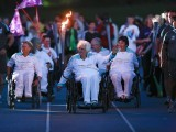 Paralympian Sally Haynes (front) carries the torch with other former Paralympians along the athletics track following the torch relay ceremony at Stoke Mandeville Stadium in Buckinghamshire August 28, 2012. PHOTO: REUTERS