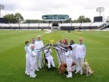 A handout picture released by the London Organising Committee of the Olympic and Paralympic Games (LOCOG) and taken on August 29, 2012, shows torchbearers posing for pictures with the paralympic flame at Lords Cricket ground in north-west London. PHOTO: AFP