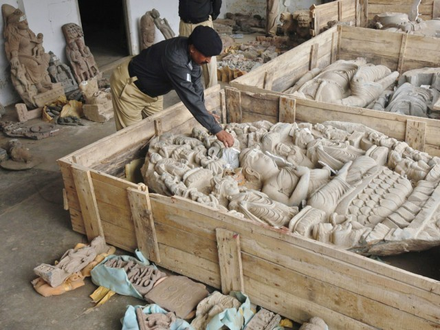 A policeman inspects seized antique artifacts, displayed for media at a police station in Karachi July 7, 2012. PHOTO: REUTERS