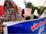 Veiled women holding placards and banners to commemorate JI's World Hijab Day. PHOTO: ONLINE