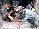 A drug addict helps inject heroin into another addict along a street in Karachi in this September 7, 2011 file photo. . PHOTO: REUTERS