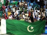 Pakistani cricket fans hold their national flag as they cheer their team.PHOTO: AFP