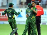 Pakistani spinner Raza Hasan (R) celebrates with skipper Mohammad Hafeez after taking the wicket of Australian batsman David Hussey. PHOTO: AFP