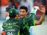 Pakistani cricketer Raza Hasan (R) celebrates with his teammate Kamran Akmal (L) after taking the wicket of Australian batsman David Hussey. PHOTO: AFP