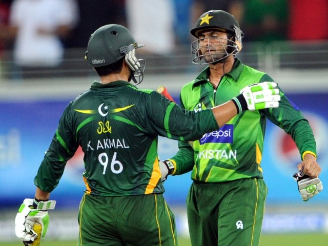 Pakistani cricketers Shoaib Malik (R) and Kamran Akmal (L) celebrate after beating Australia. PHOTO: AFP