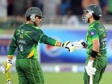 Pakistani batsman Kamran Akmal (L) touches gloves with teammate Umar Akmal after hitting a shot during the second Twenty20 international cricket match. PHOTO: AFP