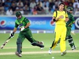 Mohammad Hafeez (R) and teammate Nasir Jamshed complete a run next to Australian bowler Mitchell Starc (C). PHOTO: AFP
