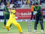 Australian batsman Matthew Wade plays a shot as Pakistani wicketkeeper Kamran Akmal looks on. PHOTO: AFP