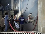 Firefighters extinguish a fire that erupted in a garment factory in Karachi on September 12, 2012.  PHOTO: AFP