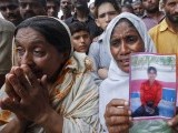 A woman holds a portrait of her son while waiting with others to identify his body, after a fire at a garment factory in Karachi September 12, 2012.  PHOTO: REUTERS