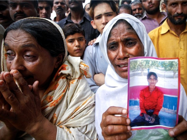 Relatives mourn the loss of their loved ones as a woman holds the photo of a victim killed in the fire. PHOTO: REUTERS