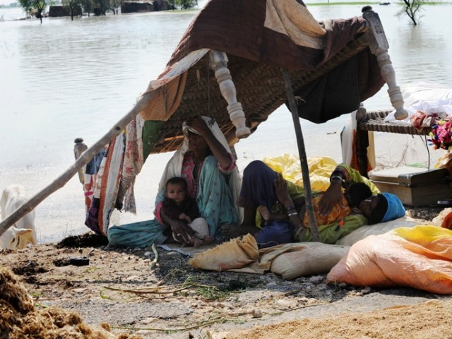 Family taking shelter on the high ground at Dera Allah yaar PHOTO:AFP