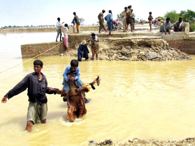 A boy takes support of his father's shoulders as he makes his way through floodwater in Dera Murad Jamali. PHOTO: AFP