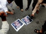 Supporters of Pakistan's outlawed Islamic hard line group Jamaat ud Dawa (JD) beat shoes on the portraits of Terry Jones, a Florida pastor during a rally against an anti-Islam movie in Lahore on September 16, 2012. PHOTO : AFP