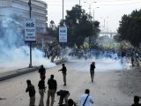 Pakistani police fire tear gas shells toward the Muslim protesters during a rally against an anti-Islam movie in Karachi on September 16, 2012.  PHOTO : AFP