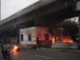A Pakistani motorcyclist rides past a burning traffic police office during a rally against an anti-Islam movie in Karachi on September 16, 2012.  PHOTO : AFP