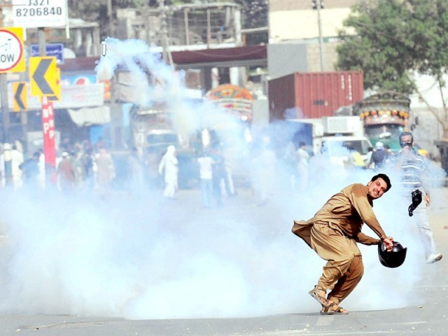 A protester retaliates against the police during a rally in Karachi. PHOTO: AFP