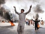 Demonstrators react beside burning tyres as they block a main highway during a protest against an anti-Islam film in Rawalpindi on September 21, 2012. PHOTO: AFP