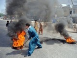 A demonstrator drags burning tyres on a street during a protest against an anti-Islam film in Rawalpindi on September 21, 2012. PHOTO: AFP