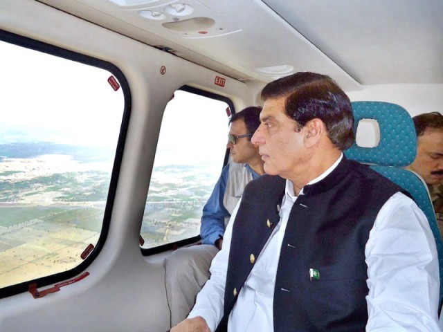 Prime Minister Raja Pervaiz Ashraf looks out the window, of a helicopter for an aerial view of the destruction wrought by recent flash floods in Rajanpur. PHOTO: APP