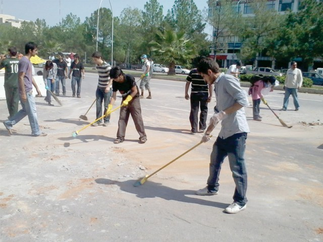Initiative: Participants of 'Project Cleanup for Peace' cleaning at the Jinnah Avenue in Islamabad. PHOTO: MUHAMMAD JAVAID/EXPRESS