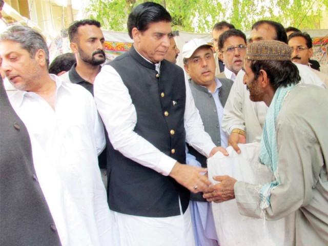 Prime Minister Raja Pervaiz Ashraf distributes relief goods among flood victims on the second day of his tour. PHOTO: PPI