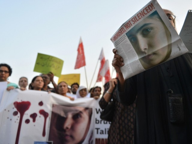Civil society activists carry placards and papers with a photograph of the gunshot victim Malala Yousafzai during a protest rally against the assassination attempt on Malala Yousafzai, in Islamabad on October 10, 2012. PHOTO: AFP
