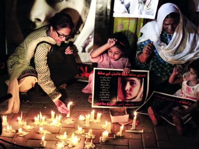 Former SCBA president Asma Jahangir lights a candle at a vigil for Malala Yousafzai on Wednesday. PHOTO: ABID NAWAZ/EXPRESS