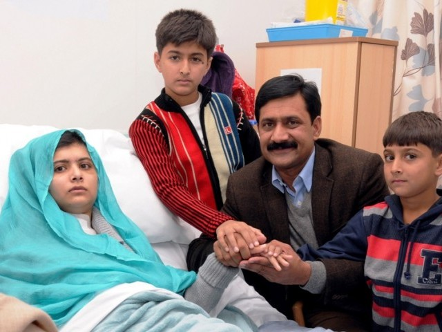 Malala Yousafzai sitting on her bed and holding hands with her brothers Khushal Khan and Apal Khan and father Ziauddin Yousufzai, at the hospital in Birmingham. PHOTO: AFP