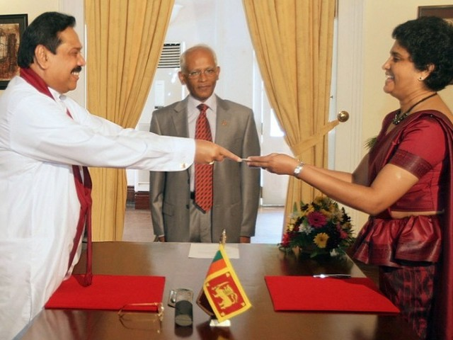 This handout photo taken on May 18, 2011 and released by Sri Lanka's Presidential Secretariat shows President Mahinda Rajapakse (L) presenting a letter of appointment to Shirani Bandaranakaye who became Sri Lanka's first woman chief justice. PHOTO: AFP