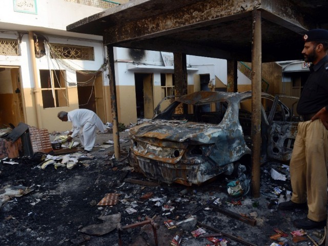 A policeman stands next to wreckage of a burnt out a car at a school that was set fire by an angry mob, following a protest alleging the school gave a test that insulted the Prophet Mohammed (pbuh), in Lahore on November 2, 2012. PHOTO: AFP