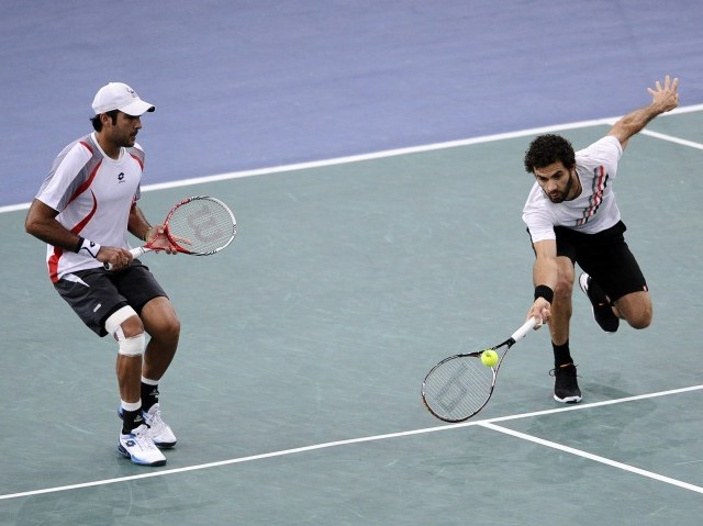 Netherlands' Rojer hits a return in front of his teammate Pakistan's Aisamul Haq (L) during their Paris Masters tournament double match against Crotia's Cilic and Brazil's Melo on November 3, 2012 at the Bercy Palais-Omnisport in Paris.   AFP PHOTO / LIONEL BONAVENTURE
