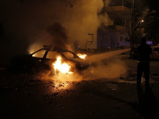 An Israeli firefighter extinguishes a burning car after a rocket fired by Palestinian militants in Gaza landed in the southern city of Beersheba November 14, 2012. PHOTO: REUTERS